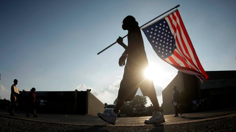 Duane Merrells walks with an upside down flag in a protest Monday, Aug. 18, 2014, for Michael Brown, who was killed by a police officer Aug. 9 in Ferguson, Mo. Brown's shooting has sparked more than a week of protests, riots and looting in the St. Louis suburb. (AP Photo/Charlie Riedel)