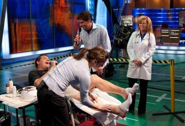 Nancy Mello watches as Mike and Mike's Mike Golic gets waxed on the set.