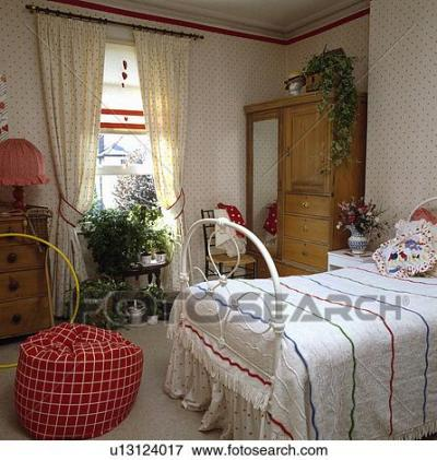 Picture of Spotted wallpaper and matching curtains at window in bedroom with red beanbag and ...
