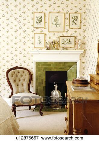 Picture of Button-back Victorian chair beside fireplace in bedroom with patterned wallpaper ...