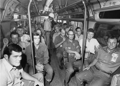 On the express bus, shipyard guard Charles Meider distributes timecards to workers. Times-Herald, August 2, 1971