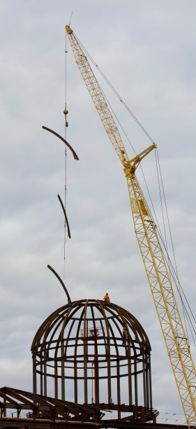 A crane lowers steel ribs to the dome to workers atop the Student Success Center at Christopher Newport University early Friday.