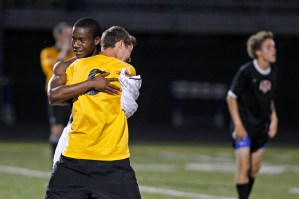 Grafton's Mikyle Valentine, left, hugs Michael Bly after defeating Nansemond River during Wednesday's 4A South region soccer semifinals at Bailey Field. Bly is usually the starting goalie but was injured for the game.