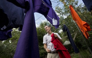 """Jim removes laundry from a backyard clothesline while doing chores during a solitary afternoon at home in late September. Jim, diagnosed with a """"mild cognitive impairment"""" precursor to Alzheimer's Disease, stopped driving this spring. He spends the days at home by himself, doing some household chores and taking care of the family dog. (Kaitlin McKeown)"""