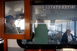 Boat captain Mark Haynie, left, navigates through the Chesapeake Bay to Tangier Island Thursday morning as Laura Hobgood, right, lab manager for White Stone Family Practice and Tangier clinic, sits patiently. (Jonathon Gruenke)