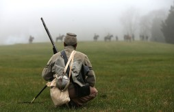 An American Civil War re-enactor dressed as a member of the North Carolina 26th infantry watches Union cavalry take their position during a re-enactment of the Battle of Appomattox Court House at the Appomattox Court House National Historical Park April 9, 2015 in Appomattox, Virginia. Today is the 150th anniversary of Confederate General Robert E. Lee's surrender of the Army of Northern Virginia to Union forces commanded by General Ulysses S. Grant in the McLean House at Appomattox, Virginia. The surrender marked the beginning of the end of the American Civil War in 1865. (Photo by Win McNamee/Getty Images)