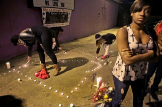 Friends and family lights candles during a vigil for Isaac Oshin outside Majik City Gentlemen's Club and Sports Bar Friday evening. Dozens of people gathered outside the club to remember Isaac Oshin who was shot to death inside the club at 5825 Jefferson Avenue Wednesday evening. (Photo by Jonathon Gruenke/Daily Press)