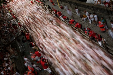 In this slow shutter speed picture, revelers run with a Jandilla's ranch fighting bull during the running of the bulls of the San Fermin festival in Pamplona, Spain, Tuesday, July 7, 2015. (AP Photo/Daniel Ochoa de Olza)