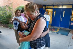 Second grade teacher Janice Baker hugs Jordyn Sharp while welcoming students to the first day of school Tuesday morning at Machen Elementary School on September 08, 2015.
