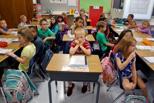 Braden Long, center, holds his head up as school administrators speak to Martha Tereska's first grade class during the first day of school Tuesday morning at Yates Elementary School on September 08, 2015.