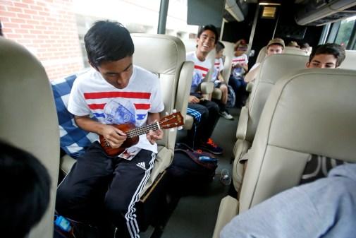 Peninsula Catholic High School student Miggy Almirante plays the ukulele while sitting on a bus Friday morning September 25, 2015. Twenty five students are traveling to Philadelphia to see Pope Francis. (Jonathon Gruenke)
