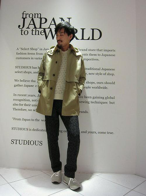 柄スラックスとオイルドコットンコートを組み合わせた男性の着こなし