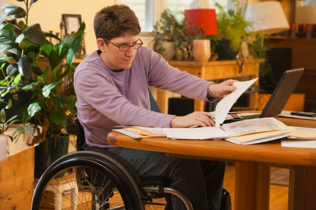 Businesswoman with multiple sclerosis doing paperwork in her accessible home --- Image by © Mark Hunt/Huntstock/Corbis