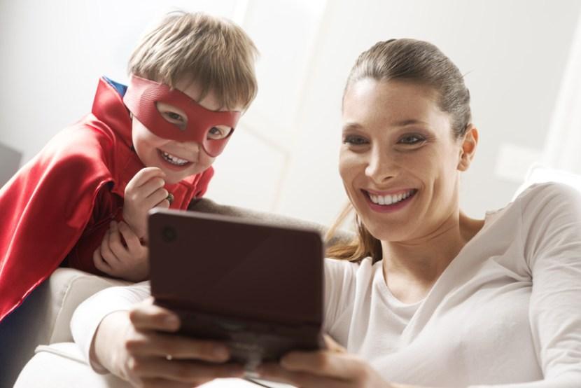 Medienkompetenz: Mutter spielt mit ihrem als Superheld verkleideten Sohn Videospiele