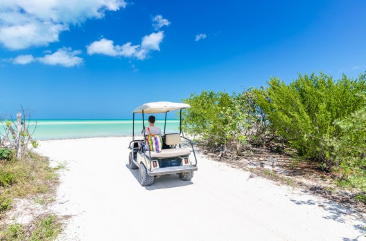 Cute young man driving golf cart back view at tropical white sandy beach during his Caribbean vacation on Holbox island, Mexico