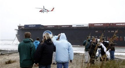AP Photo/Steve HelberA US Coast Guard helicopter prepares to lower two salvage crewmen onto a large barge that broke free is on the beach near the Sandbridge fishing pier in the Sandbridge area of Virginia Beach, Va., Friday, Nov. 13, 2009.