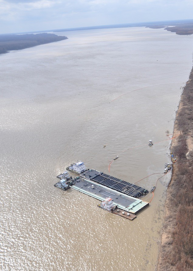VICKSBURG, Miss. – Unified Command response vessels skim oil released from the MOC-12 barge in the Mississippi River near mile marker 436 Tuesday.  Response crews have deployed 2,800 feet of  boom to contain the source of the oil leak.  U.S. Coast Guard photo.