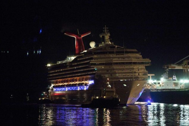 The Carnival Triumph cruise ship is towed towards dock at the port of Mobile