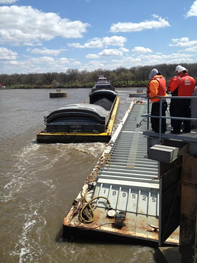 Members of the Unified Command watch as one of three additional barges is removed from near the Marseilles Dam in Marseilles, ill., during continued salvage operations, April 25, 2015.