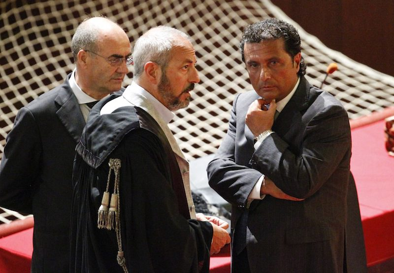 Francesco Schettino (R), captain of the Costa Concordia cruise ship, talks with his lawyers during a trial in Grosseto, central Italy, July 17, 2013.