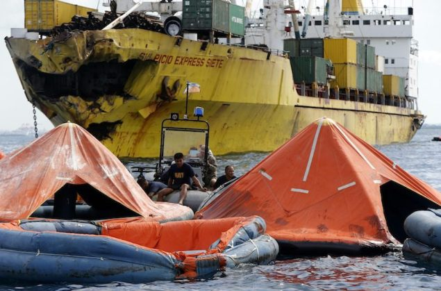 Philippine's Navy rescuers wait for divers, who are searching for survivors and bodies from the sunk ferry that collided with a cargo vessel (background) on Friday, in Talisay, Cebu August 17, 2013. A Philippine ferry sank after colliding with a container ship owned by a company involved in the world's worst peacetime maritime disaster, killing at least 24 people and leaving more than 200 missing, the coast guard said on Saturday.    REUTERS/Erik De Castro