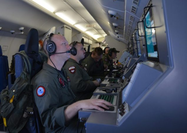 Crew members on board a P-8A Poseidon assigned to Patrol Squadron (VP) 16 man their workstations while assisting in search and rescue operations for Malaysia Airlines flight MH370, March 16, 2014. U.S. Navy Photo