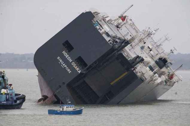 The cargo ship Hoegh Osaka lies on its side after being deliberately ran aground on the Bramble Bank in the Solent estuary, near Southampton in southern England January 5, 2015. REUTERS/Peter Nicholls