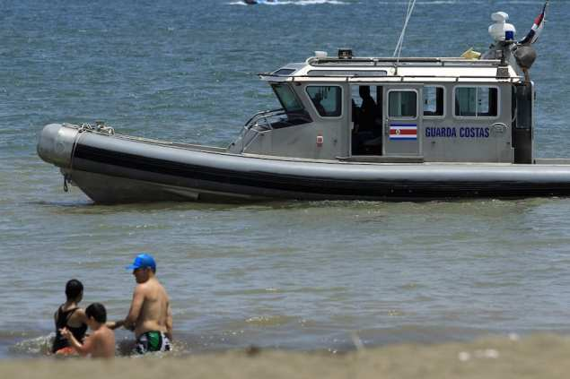 A Coast Guard boat warns bathers of the dangers of swimming in the sea in Puntarenas May 3, 2015.