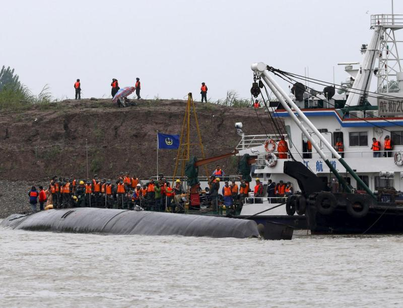 Rescue workers and a capsized ship are seen during a media trip to the site of the sinking, organized by the Chinese goverment, in the Jianli section of Yangtze River, Hubei province