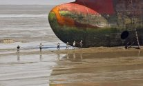 File photo of workers carrying a rope line to fasten a decommissioned ship at the Alang shipyard in Gujarat