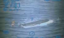 A U.S. Coast Guard rescue swimmer inspects the 19-foot boat belonging to the boys, Sunday, July 26, 2015. U.S. Coast Guard Photo