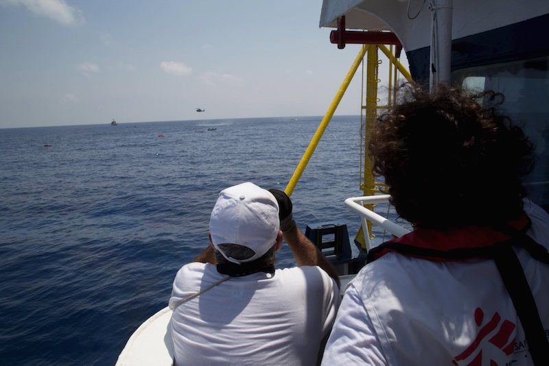 Medecins san Frontiere (MSF) Field coordinator Juan and first officer Porfirio follow the rescue operation involving ships and sea rescue helicopters, scanning the area to spot survivors in the water where a boat carrying migrants capsized and sank with many feared drowned off the coast of Libya August 5, 2015.  A boat packed with up to 700 African migrants capsized in the Mediterranean Sea off the coast of Libya on Wednesday and many were feared dead, officials and aid agencies said.  REUTERS/Marta Soszynska/MSF/ HandoutATTENTION EDITORS - NO SALES. NO ARCHIVES. FOR EDITORIAL USE ONLY. NOT FOR SALE FOR MARKETING OR ADVERTISING CAMPAIGNS. THIS IMAGE HAS BEEN SUPPLIED BY A THIRD PARTY. IT IS DISTRIBUTED, EXACTLY AS RECEIVED BY REUTERS, AS A SERVICE TO CLIENTS. REUTERS IS UNABLE TO INDEPENDENTLY VERIFY THE AUTHENTICITY, CONTENT, LOCATION OR DATE OF THIS IMAGE.