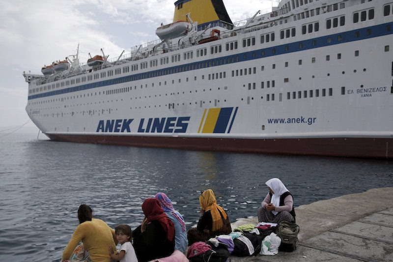 "A group of Syrian women sit at the dock of the port of Kos as migrants and refugees wait next to the passenger ship ""Eleftherios Venizelos"" at the port of the Greek island of Kos, August 15, 2015. The Eleftherios Venizelos vessel will house more than 2500 migrants who entered the Greece from the Turkish coast and will be used as a registration center for migrants.The United Nations refugee agency (UNHCR) called on Greece to take control of the ""total chaos"" on Mediterranean islands, where thousands of migrants have landed. About 124,000 have arrived this year by sea, many via Turkey, according to Vincent Cochetel, UNHCR director for Europe.  REUTERS/Alkis Konstantinidis"