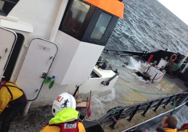 Lifeboat volunteers help pump the vessel out. Credit: RNLI/Peterhead