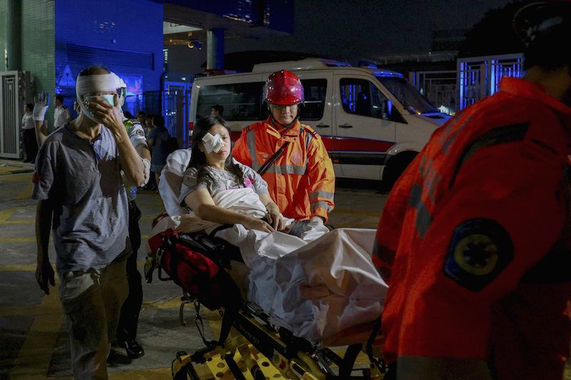Injured ferry passengers are escorted by rescuers after getting onshore in Hong Kong, China October 25, 2015. REUTERS/Stringer