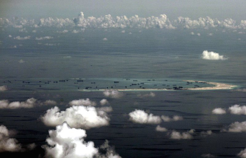 An aerial photo taken through a glass window of a Philippine military plane shows the alleged on-going land reclamation by China on mischief reef in the Spratly Islands in the South China Sea, west of Palawan, Philippines, in this May 11, 2015 file photo. When a U.S. Navy guided-missile destroyer sailed near one of Beijing's artificial islands in the disputed South China Sea this week, it was operating in a maritime domain bristling with Chinese ships. While the U.S. Navy is expected to keep its technological edge in Asia for decades, China's potential trump card is sheer weight of numbers, with dozens of naval and coastguard vessels routinely deployed in the South China Sea. REUTERS/Ritchie B. Tongo/Pool/Files