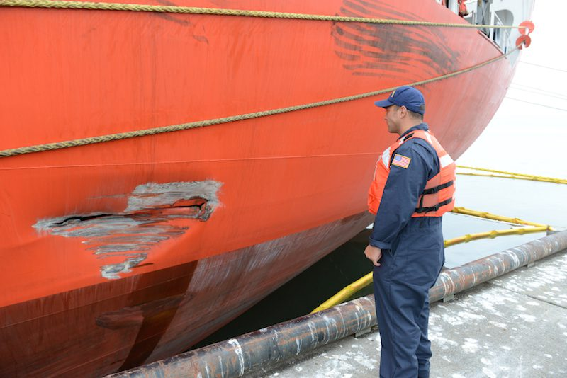 Petty Officer 2nd Class Mark Campanale, marine science technician at Coast Guard Sector Columbia River, surveys the damage done to the MV Global Gold after it allided with Pier 1 in the Port of Astoria, Ore., and spilled 1,100 gallons of diesel fuel, Oct. 2, 2015. U.S. Coast Guard Photo