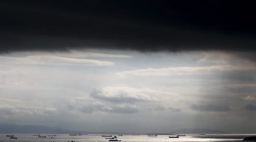 Cargo ships are seen sailing under storm clouds in the sea near the port of Piraeus in Athens, Greece in this March 5, 2015 file photo. REUTERS/Alkis Konstantinidis