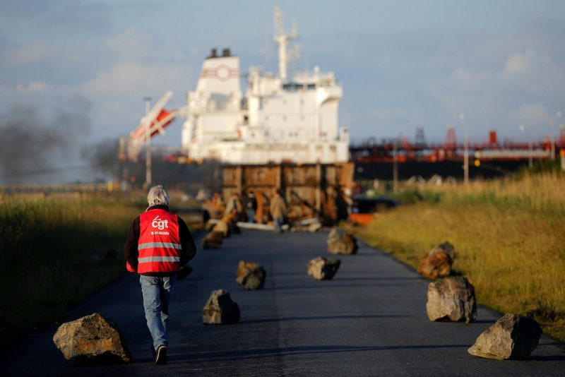A French CGT labour union employee walks near a barricade to block the entrance of the fuel depot of the society SFDM near the oil refinery of Donges, France, May 23, 2016. REUTERS/Stephane Mahe