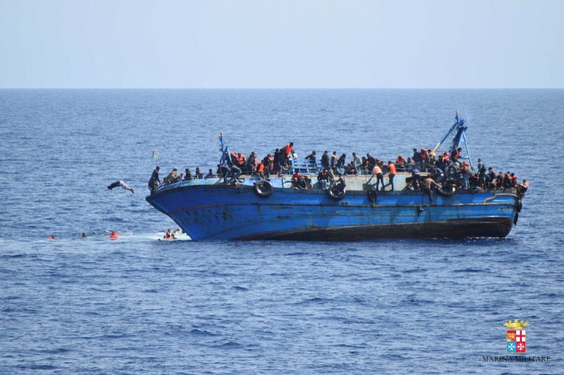 """Migrants are seen on a capsizing boat before a rescue operation by Italian navy ships """"Bettica"""" and """"Bergamini"""" (unseen) off the coast of Libya in this handout picture released by the Italian Marina Militare on May 25, 2016. Marina Militare/Handout via REUTERS"""