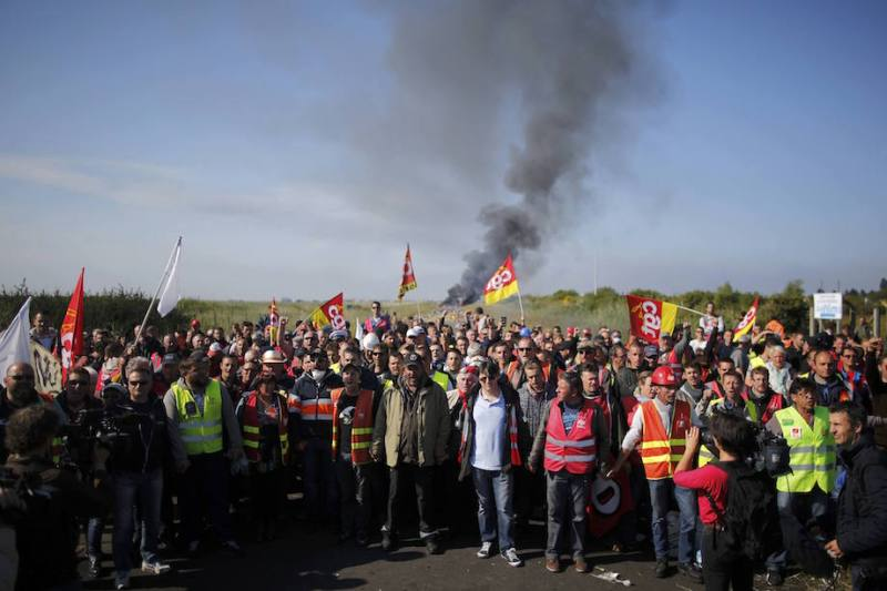 Striking French CGT labour union employees stand near a burning barricade before a police operation to free up a fuel depot near the Donges oil refinery as workers protest the labour reforms law proposal in Donges, France, May 27, 2016. REUTERS/Stephane Mahe