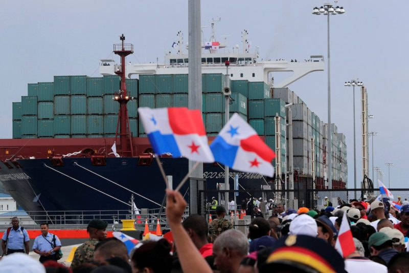 People wave Panama flags as they wait for the Chinese COSCO container vessel named Andronikos to navigate through the Agua Clara locks during the first ceremonial pass through the newly expanded Panama Canal, June 26, 2016. REUTERS/Carlos Jasso TPX IMAGES OF THE DAY