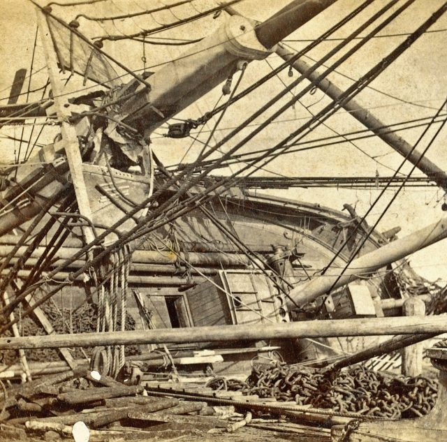 View of deck and masts of a whale ship on its side for repairs