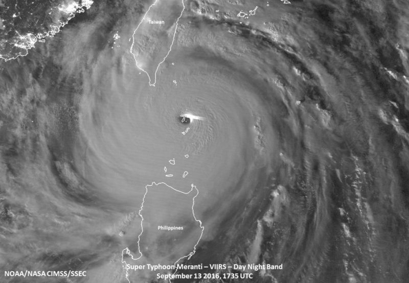 "Early on Sept. 14, the Suomi NPP satellite captured this image that shows Super Typhoon Meranti as it hit the island of Itbayat in the Luzon Strait. The waxing gibbous (93% of full) moon provided quite a bit of illumination for the Day Night Band on VIIRS to observe quite a number of features, including (tropospheric) gravity waves emanating from the very well defined eye, mesovorticies within the eye itself and a lone lightning ""streak"" near the eyewall itself. Credits: NASA/NOAA/NRL"