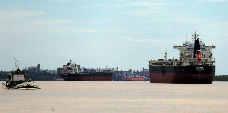 Ships used to carry grains for export are seen next to a dredging boat (L) on the Parana river near Rosario, Argentina, January 31, 2017. Picture taken January 31, 2017. REUTERS/Marcos Brindicci