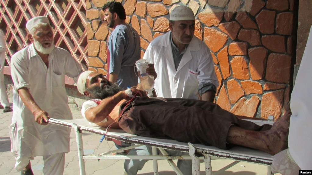 Afghan men carry an injured man to a hospital after a suicide attack in Nangarhar Province on September 11.