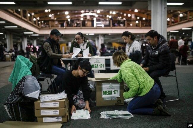 Funcionarios electorales cuentan los votos el domingo, 26 de agosto de 2018 en Bogotá, tras el cierre de las urnas en un referendum para disminuir la la corrupción.