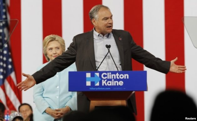 Democratic U.S. presidential candidate Hillary Clinton listens to her choice for running mate, Senator Tim Kaine of Virginia, after she introduced him during a campaign rally in Miami, Florida, July 23, 2016.