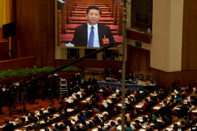 FILE - Chinese President Xi Jinping is displayed on a large screen during the opening session of the annual National People's Congress in Beijing's Great Hall of the People, March 5, 2016.