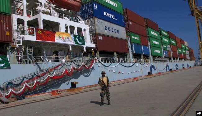 A Pakistan soldier stands guard while a loaded Chinese ship prepares to depart Gwadar port, about 700 kilometers (435 miles) west of Karachi. Nov. 13, 2016.